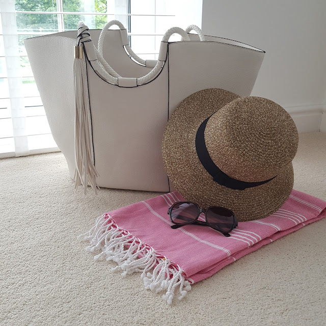 A white beach bag with a straw hat and hammam towel