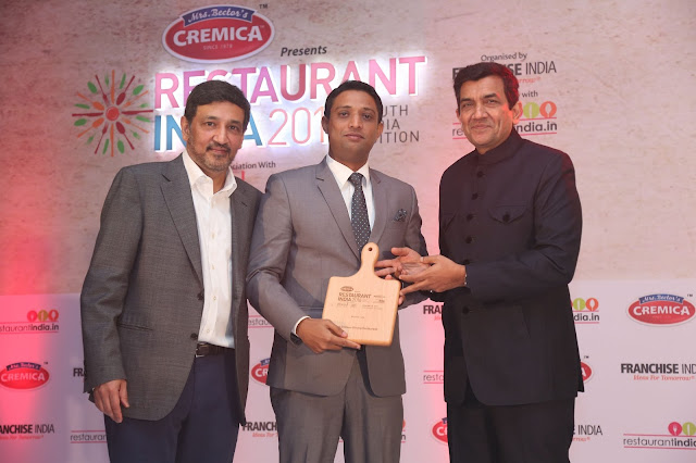 Mr. Ganeshan Maniyan receiving the award from Master Chef Sanjeev Kapoor