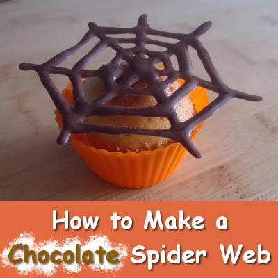 Cupcake in orange wrapper with spiderweb chocolate topper