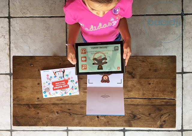 Fille qui utilise l'appli Blink Book sur sa tablette pour animer un coloriage nounours