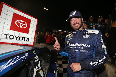 Martin Truex Jr, Driver of the #19 Auto Owners Insurance Toyota, Poses with  the Winners Sticker after the Monster Energy #NASCAR Cup Series Toyota Owners 400