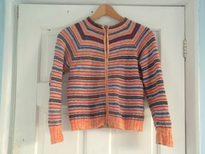 A colorfully striped cardigan on a hanger