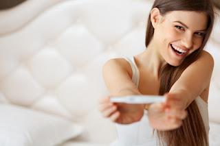 Mulher feliz a segurar um teste de gravidez na mão