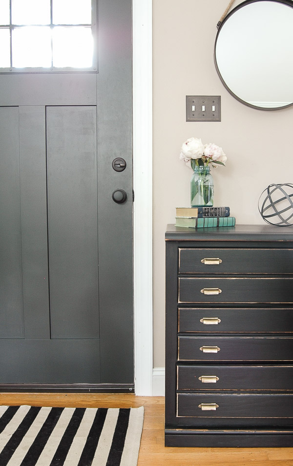 Dark gray entryway door with black multi drawer chest.