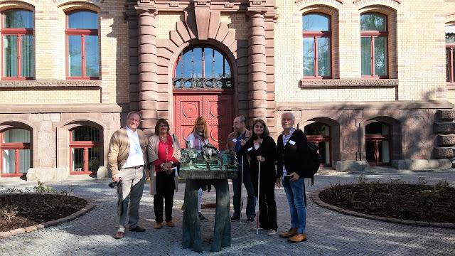 Fotografia do grupo de participantes e tutores junto ao mapa tátil do recinto do centro