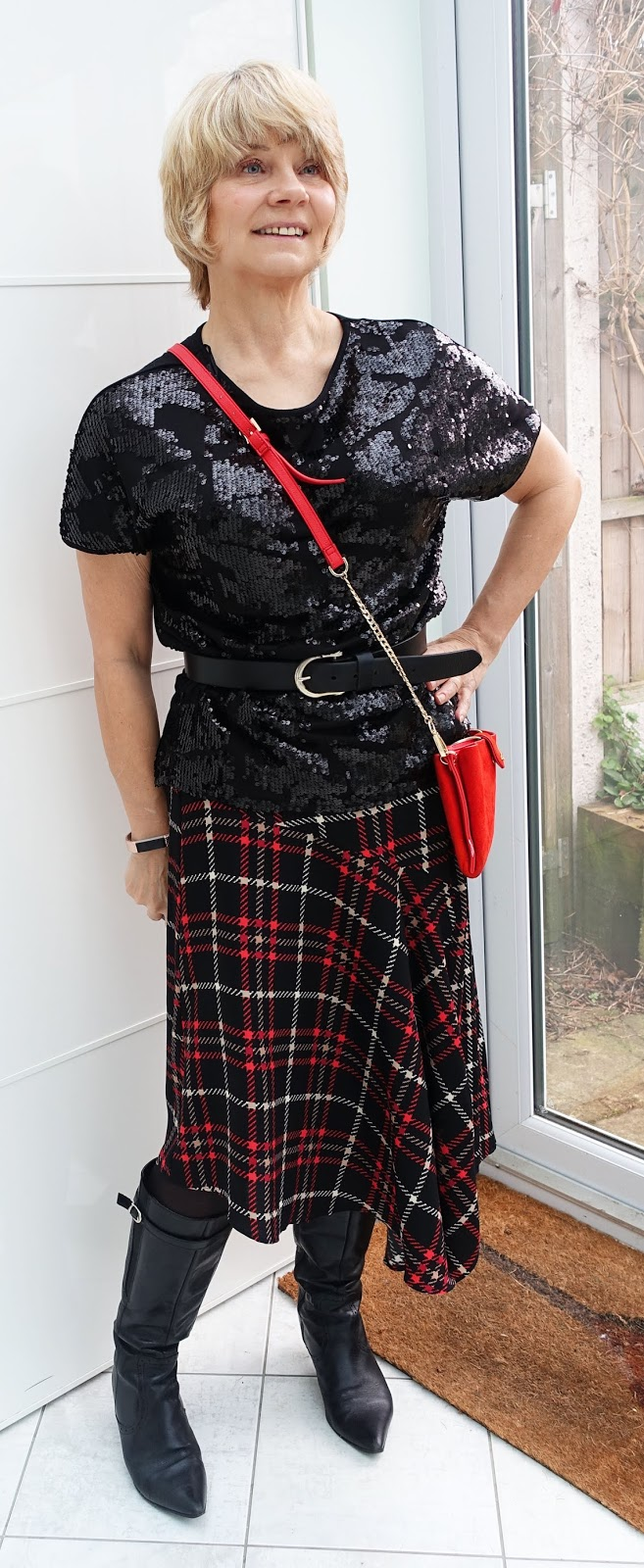 Fashion blogger Gail Hanlon in black sequin top, plaid asymmetric skirt and kitten heel boots
