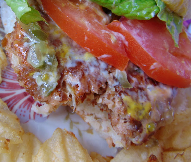 A close up view of a Veggie Burger with Vegetarian Burger in a bun with lettuce, tomato and condiments, served with potato chips.
