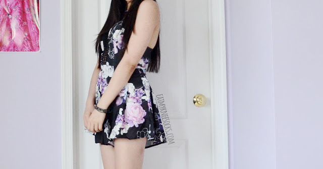 The Carlotta romper in black floral from Selfie Leslie, featuring a blue-and-purple watercolor rose print, crochet lace cutouts, fit-and-flare shape, flowy shorts, sweetheart bust, and strappy cutout neckline.