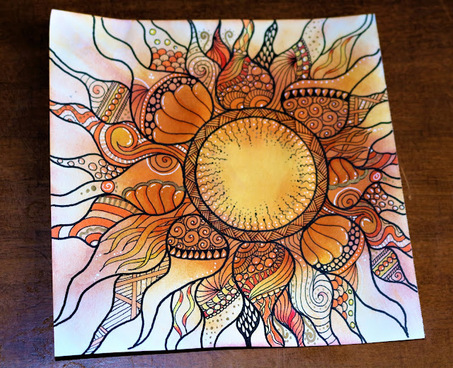 Zentangle sun with distress ink background