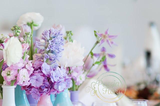 Fioletowe kwiaty na stołach weselnych