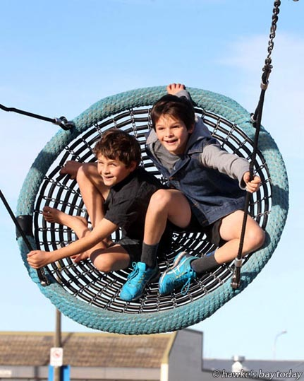 L-R: Nathan Medina, 8, Jack Medina, 10, Napier, playing on a swing at Taradale Park, Taradale, Napier, in the warm late afternoon sun, weather. photograph
