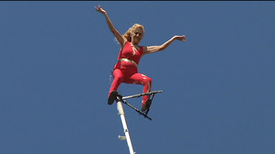 She performs a breathtaking stunt at the top of a pole without safety device