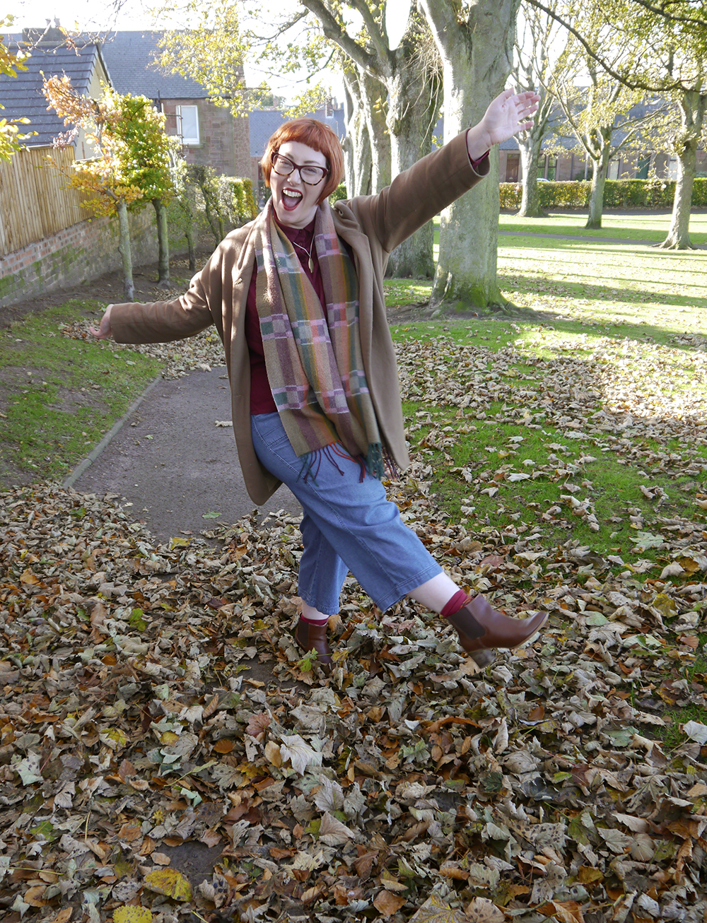 Kickin up leaves in the park while wearing an outfit of autumn colours