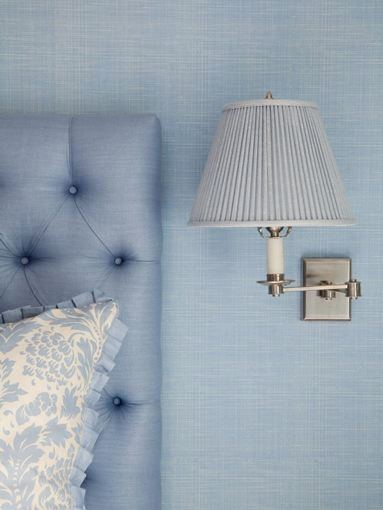 Detail of the headboard and accent pillow as well as small wall mounted reading lamp