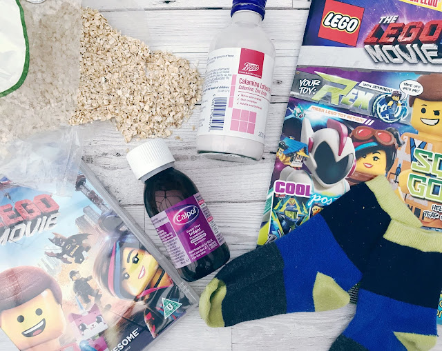 Flatlay showing porridge oats, calamine lotion, calpol, lego magazine and dvd and a pair of socks