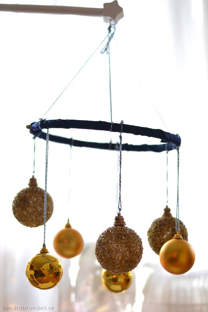 Gör en egen mobil till spjälsängen av julgranskulor och band.