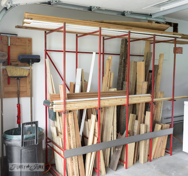 Red metal rack with lots of pieces of wood on it. garage with brooms