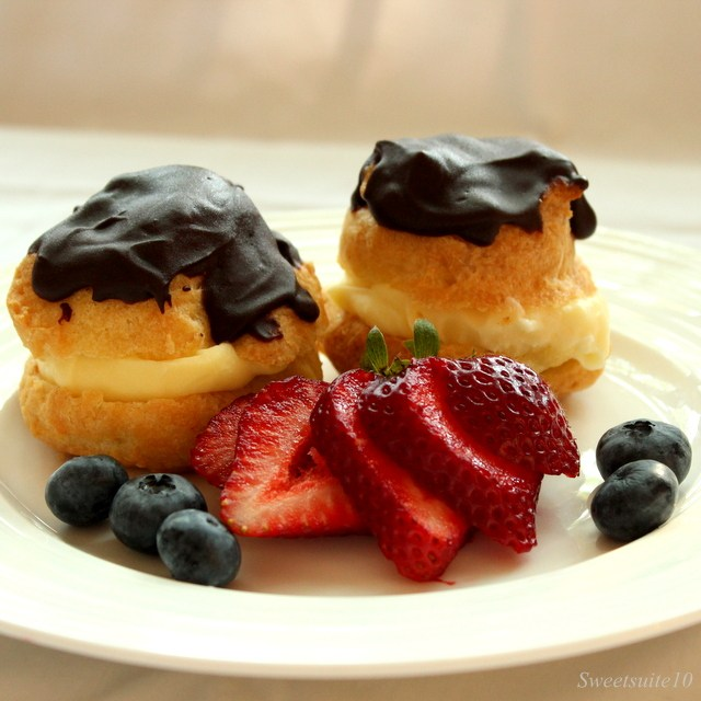 Two almond cream puffs on a plate