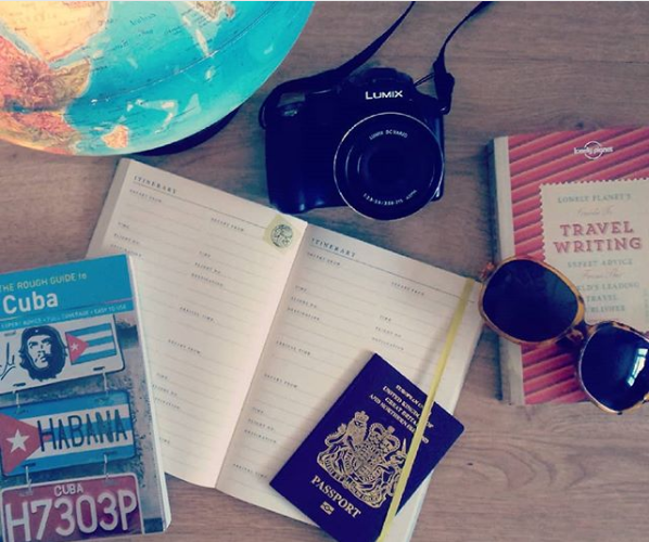 Travel planning, including globe, notebook, passport and Cuba travel guide