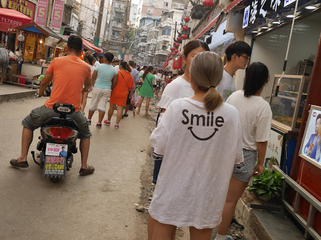"""Smile"" with a smile below on the back of shirt worn by a young woman"
