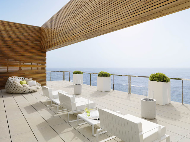 Balcony with white chairs overlooking the ocean