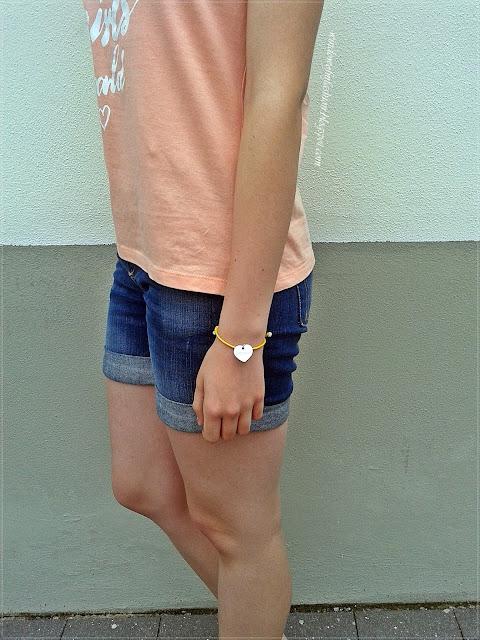 Brzoskwiniowy T-shirt, jeansowe krótkie spodenki, bransoletka z serduszkiem