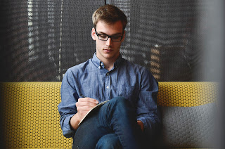 A man with glasses writing in a notebook