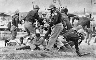 """March 7, 1965, known as """"Bloody Sunday,"""" Civil Rights marchers in Selma, A burly trooper swings at John Lewis's head."""