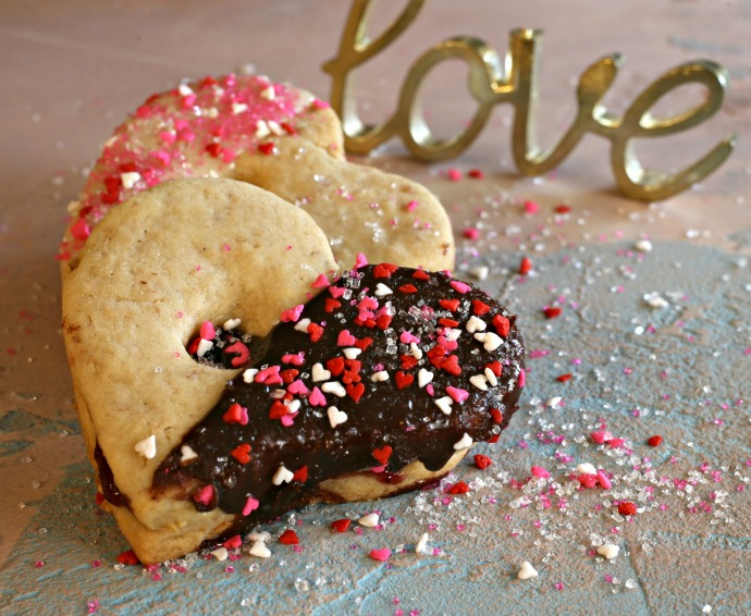 Heart shaped peanut linzer cookies topped with chocolate and sprinkles.
