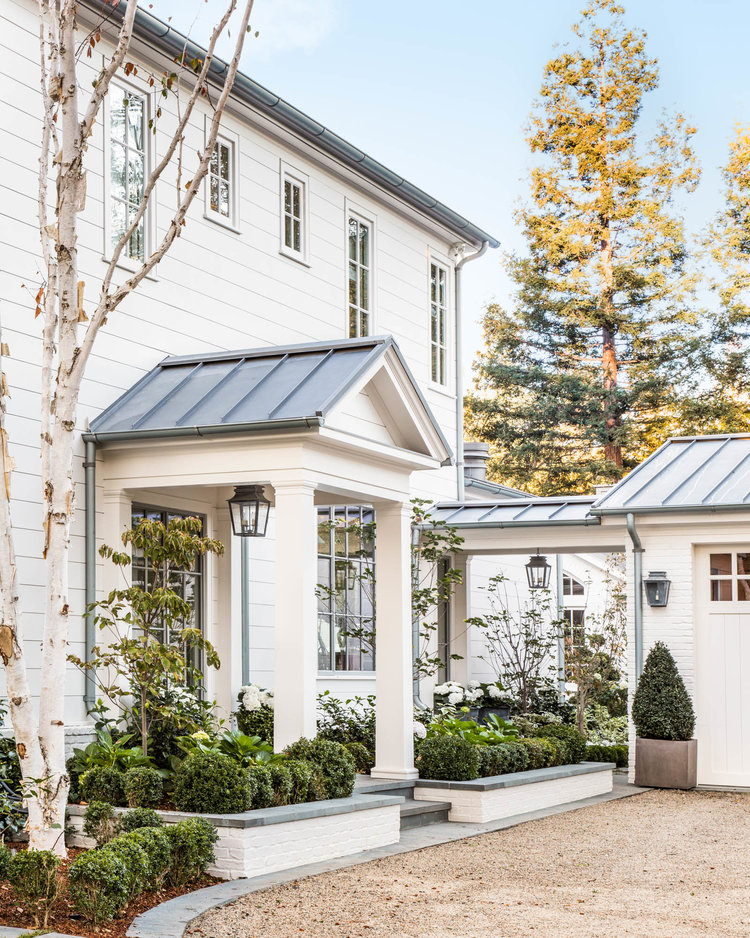 Stunning curb appeal at entrance of white farmhouse with metal roof in California