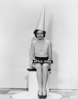 Black and white picture of a brunette woman in a white dunce cap seated and holding an April Fool sign.