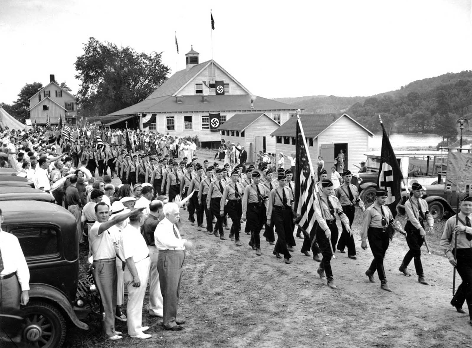 Nearly 1,000 uniformed men wearing swastika arm bands and carrying Nazi banners parade past a reviewing stand in New Jersey on July 18, 1937. The New Jersey division of the German-American Bund opened its 100-acre Camp Nordland at Sussex Hills. Dr. Salvatore Caridi of Union City, spokesman for a group of Italian-American Fascists attending as guests, addressed the bund members as