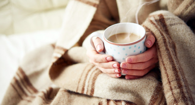 a woman enjoys a hot cup of cocoa because her furnace is broke and needs repair in Plymouth Indiana