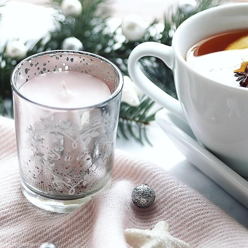 zimowa dekoracja ze świecą, filiżanką herbaty i świerkową gałązką