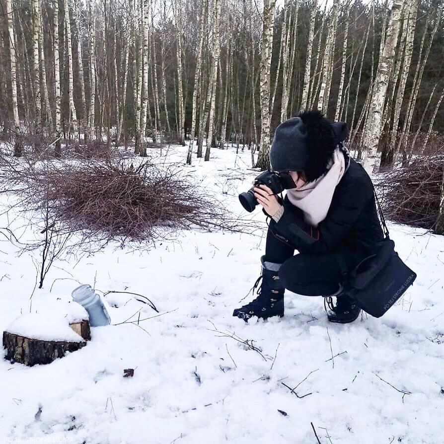 kobieta z aparatem robi zdjęcia w lesie zimą