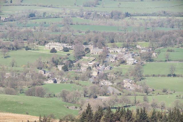 A view of Downham from Pendle Hill - stone cottages, the church and surrounding farmland.