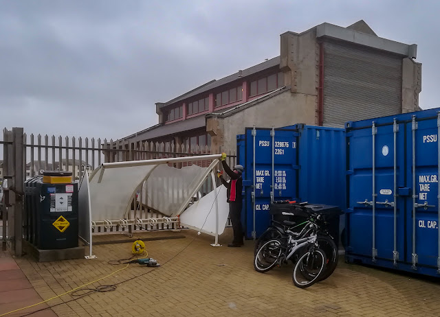 Photo of work underway to take down the damaged bike shelter