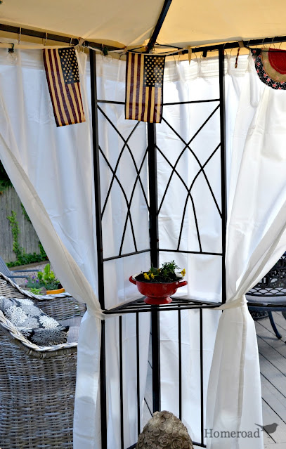 corner of a gazebo with white curtains and flags