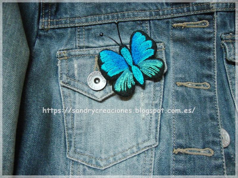ejemplo de colocación del broche mariposa azul en la solapa del bolsillo de una cazadora tejana