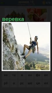 альпинист поднимается высоко по горе на веревке в каске