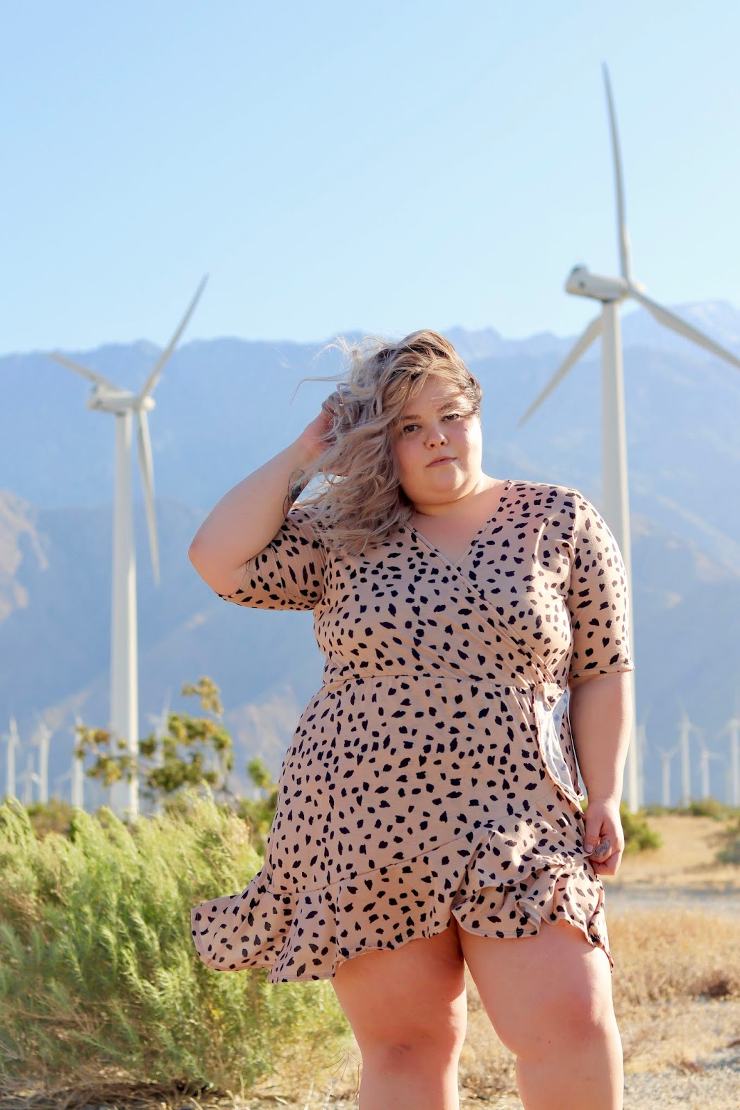 Chicago Plus Size Petite Fashion Blogger, YouTuber, and model Natalie Craig, of Natalie in the City, reviews Pink Clove's mini wrap dress and attends Her Conference in Los Angeles. palm springs windmills, best places to take photos in palm springs