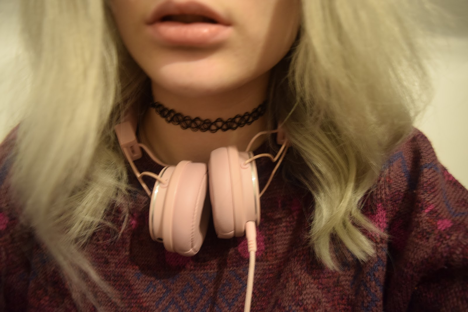 girl with silver hair wearing headphones round her neck