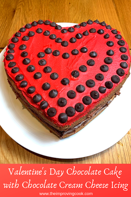 close up of a heart shaped chocolate sandwich cake with red icing decorated with chocolate chips