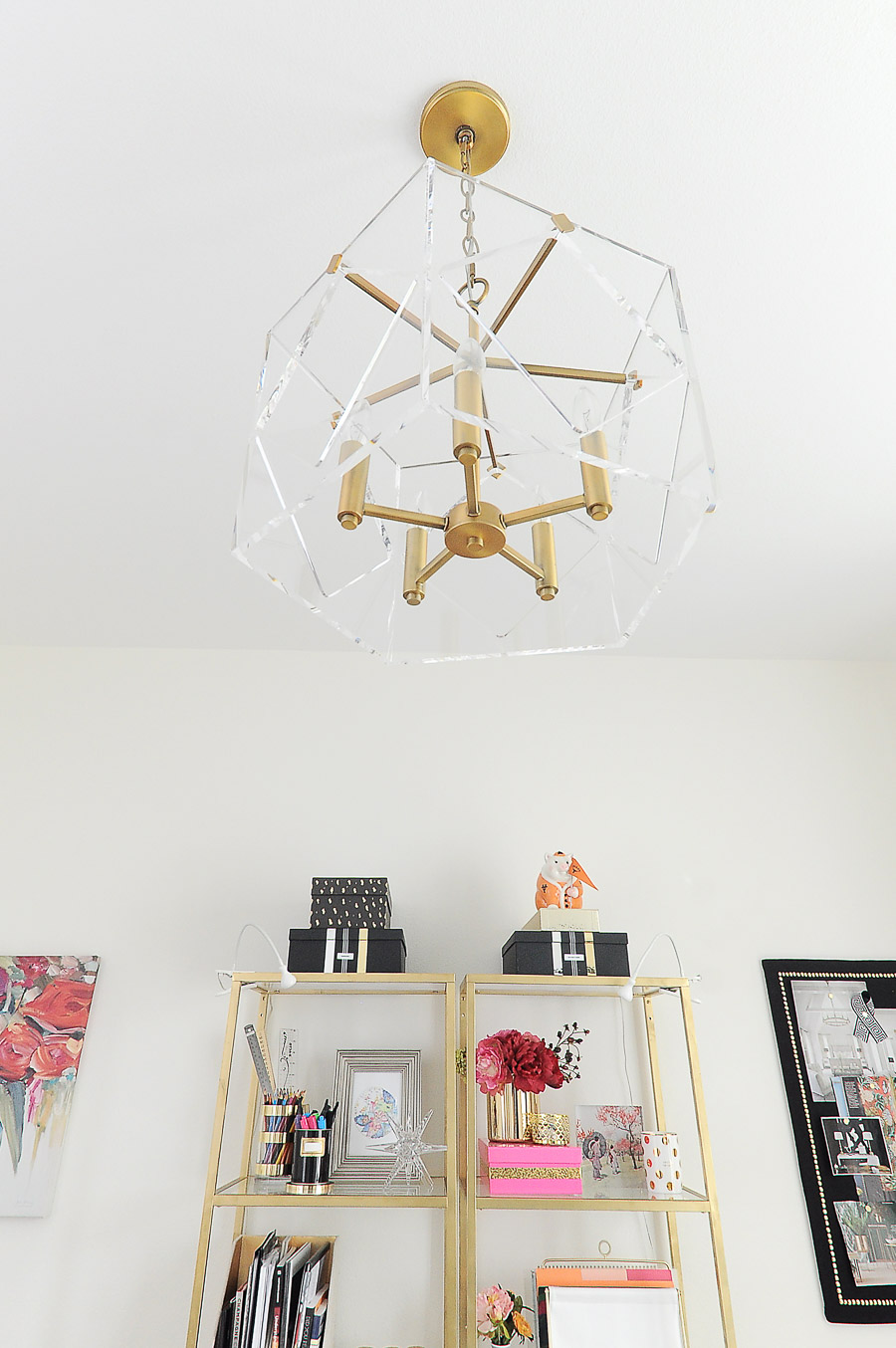 A lucite and brass chandelier adds glamour to a bright white and gold home office space.