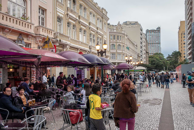 Cena na Rua XV de Novembro com pessoas nas mesas dos restaurantes na calçada e crianças vendendo doces