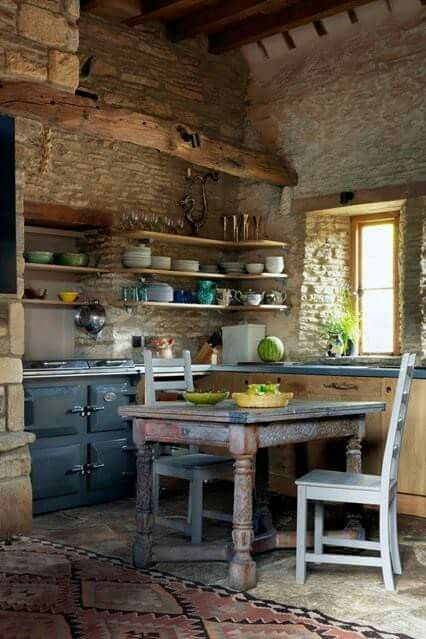 Rustic European farmhouse kitchen with stone walls and weathered farm table