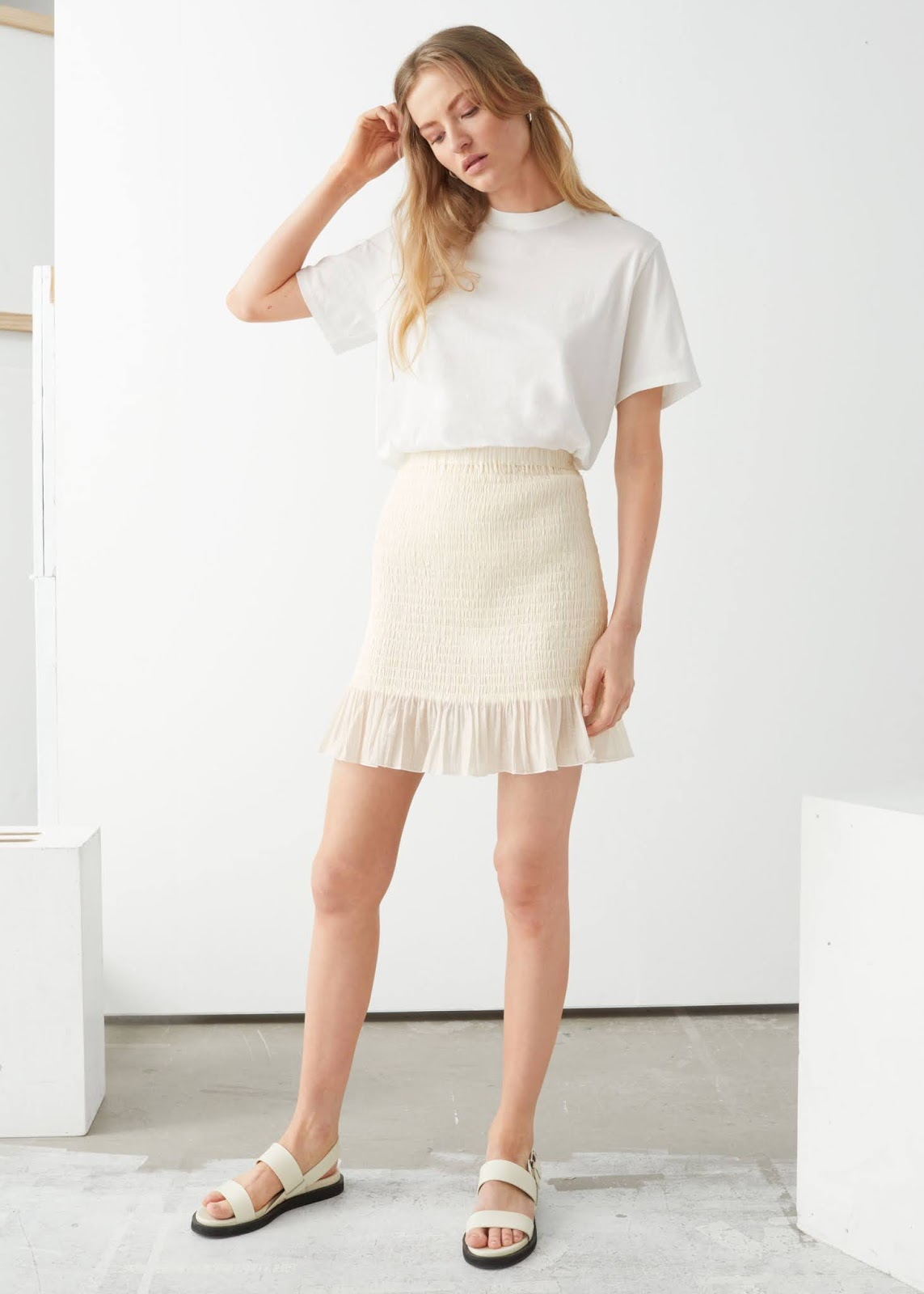 Stylish Summer Outfit Idea: White T-Shirt, Under-$100 Mini Skirt With Smocked Detailing, and Flat Sandals.