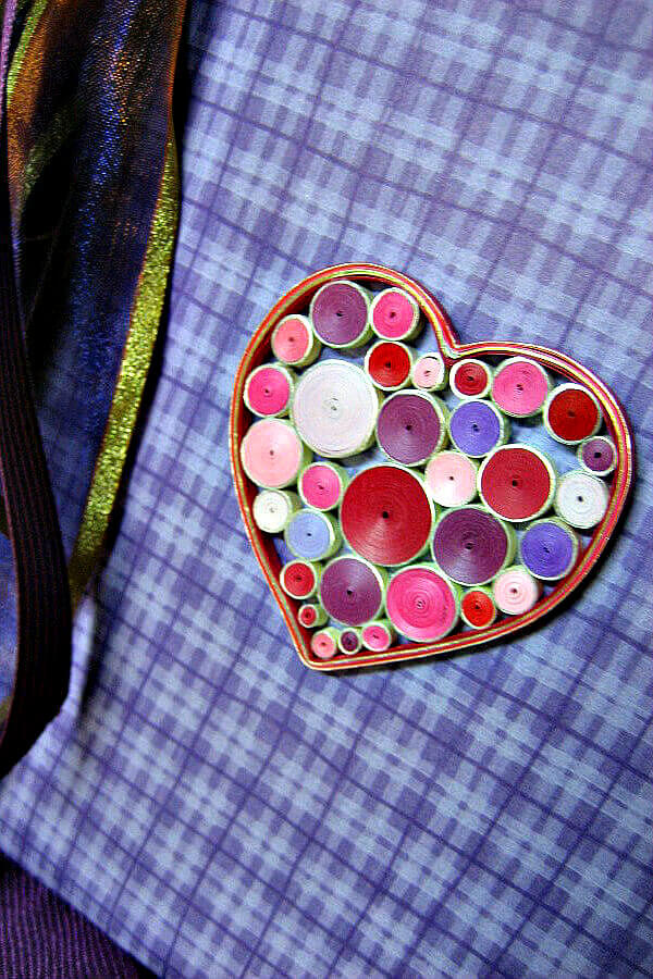 quilled heart outline filled with pink, purple, red and white tight coils