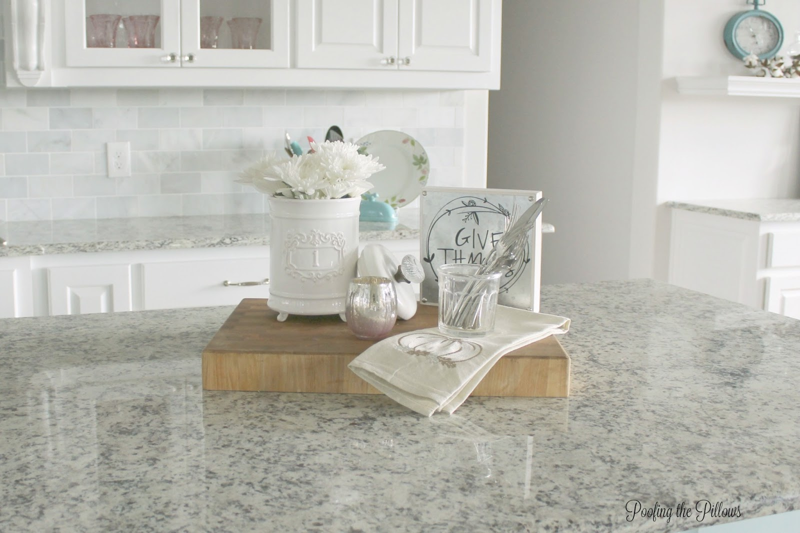 A beautiful kitchen vignette created on an old cutting board, canister, and fresh flowers.