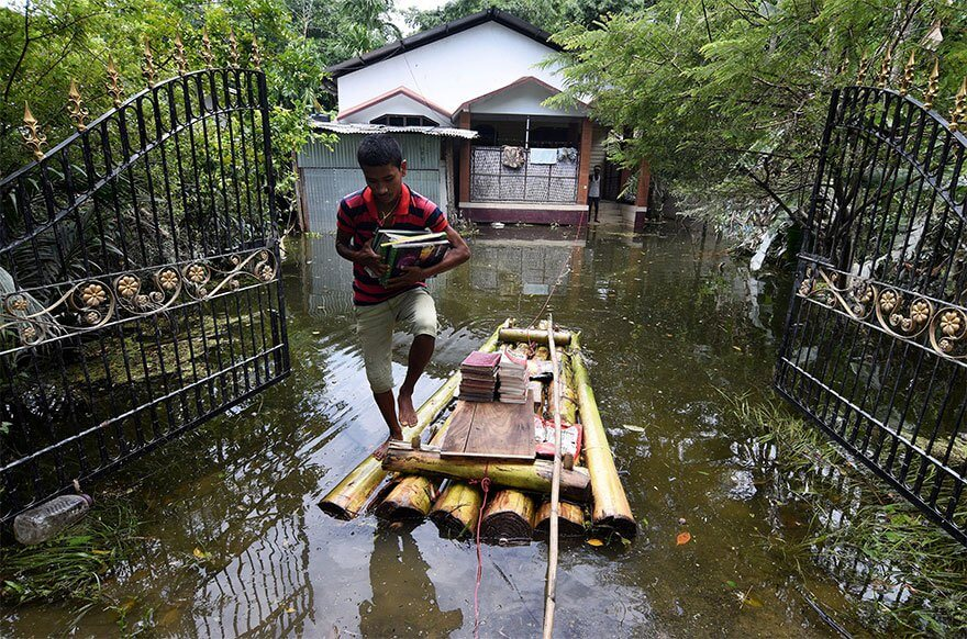 18 Devastating Pictures Of The Flooding In South Asia That Will Shock You - A Boy Uses A Banana Raft To Transport His Books In Jakhalabandha Area In Nagaon District, In The Northeastern State Of Assam, India